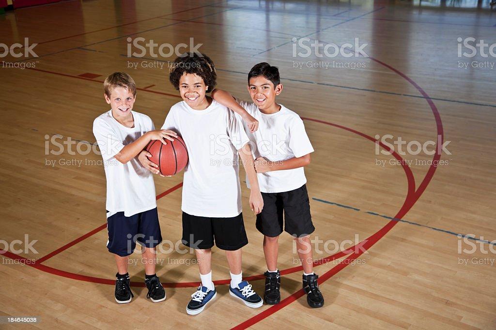 Boys in school gymnasium holding basketball stock photo