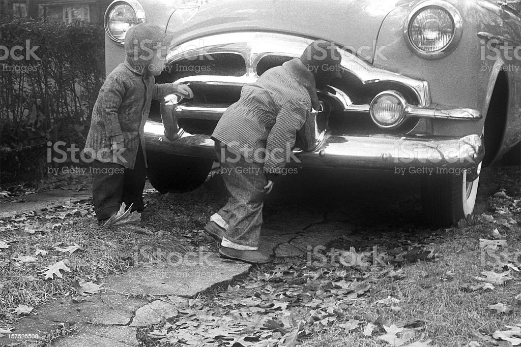 boys inspecting Packard Coupe car 1955, retro royalty-free stock photo