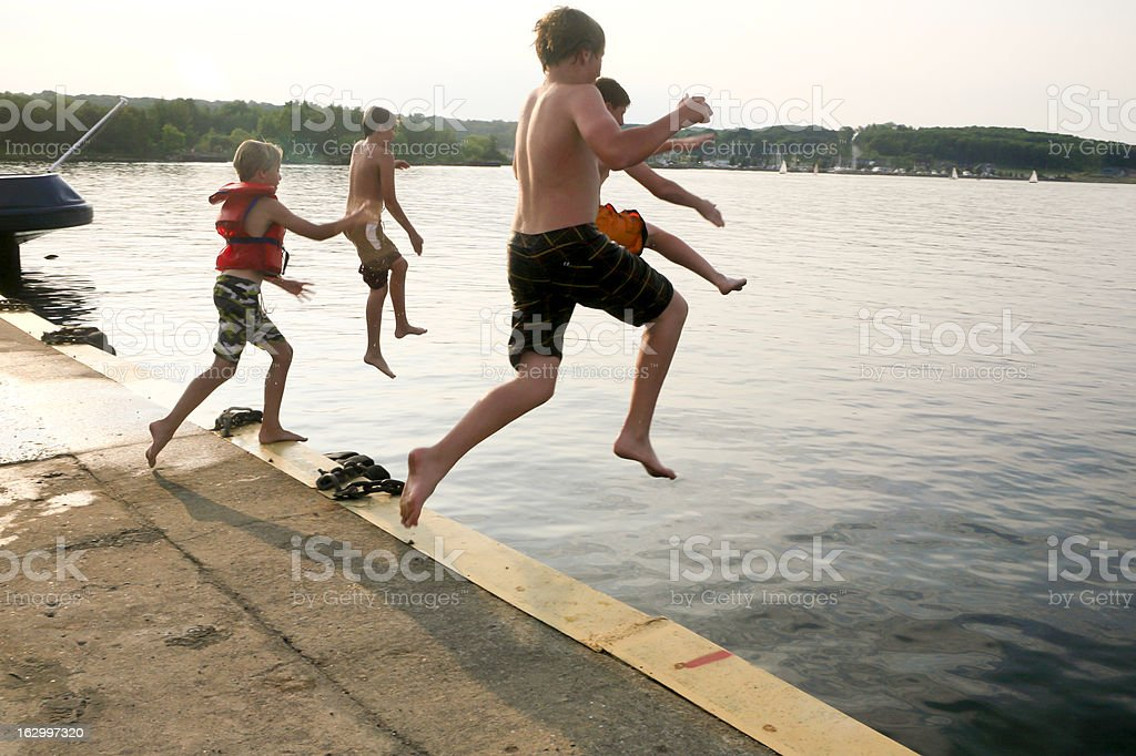 Boys Jumping into the water stock photo
