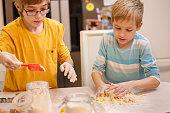 Boys kneading dough together