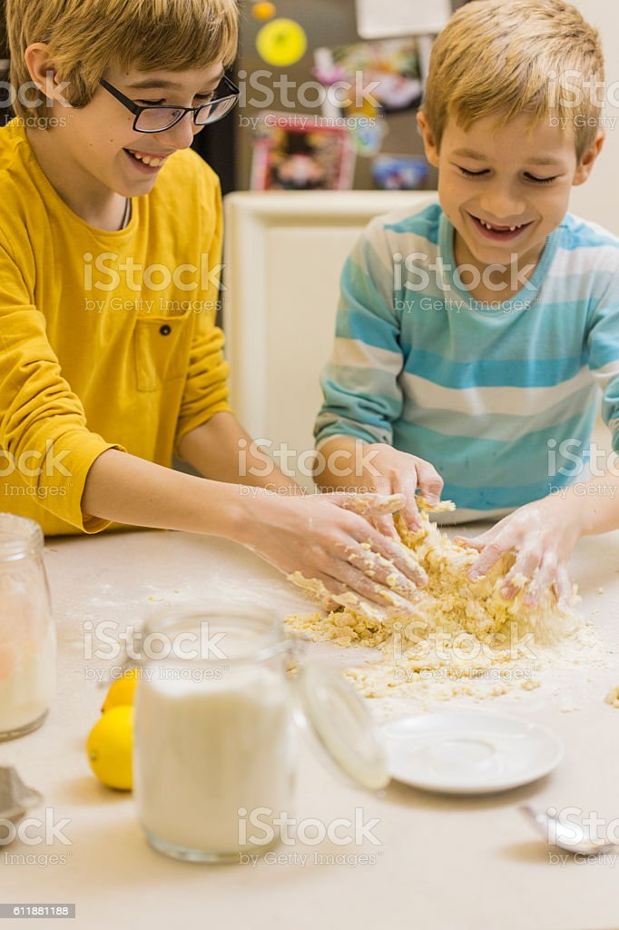 Boys kneading dough together stock photo