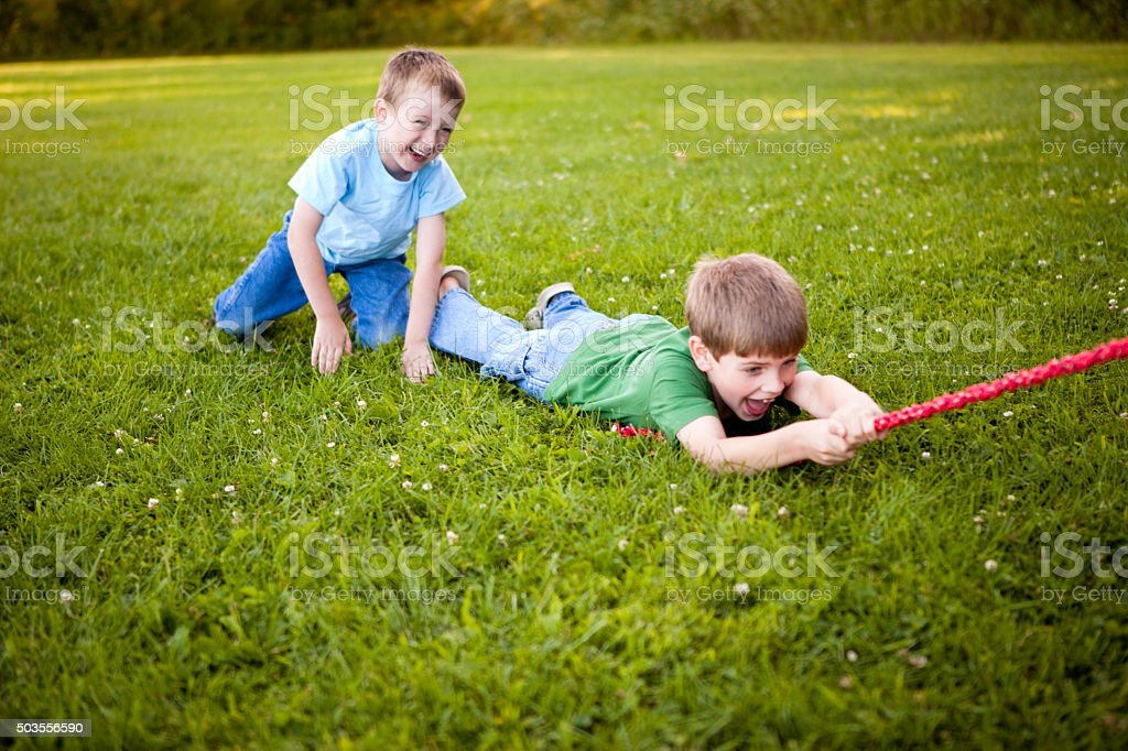 Boys Laughing Outside While Playing Tug-Of-War stock photo