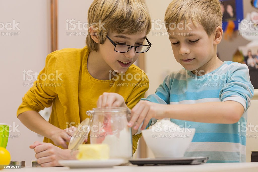 Boys measuring flour on weight scale in the kitchen stock photo