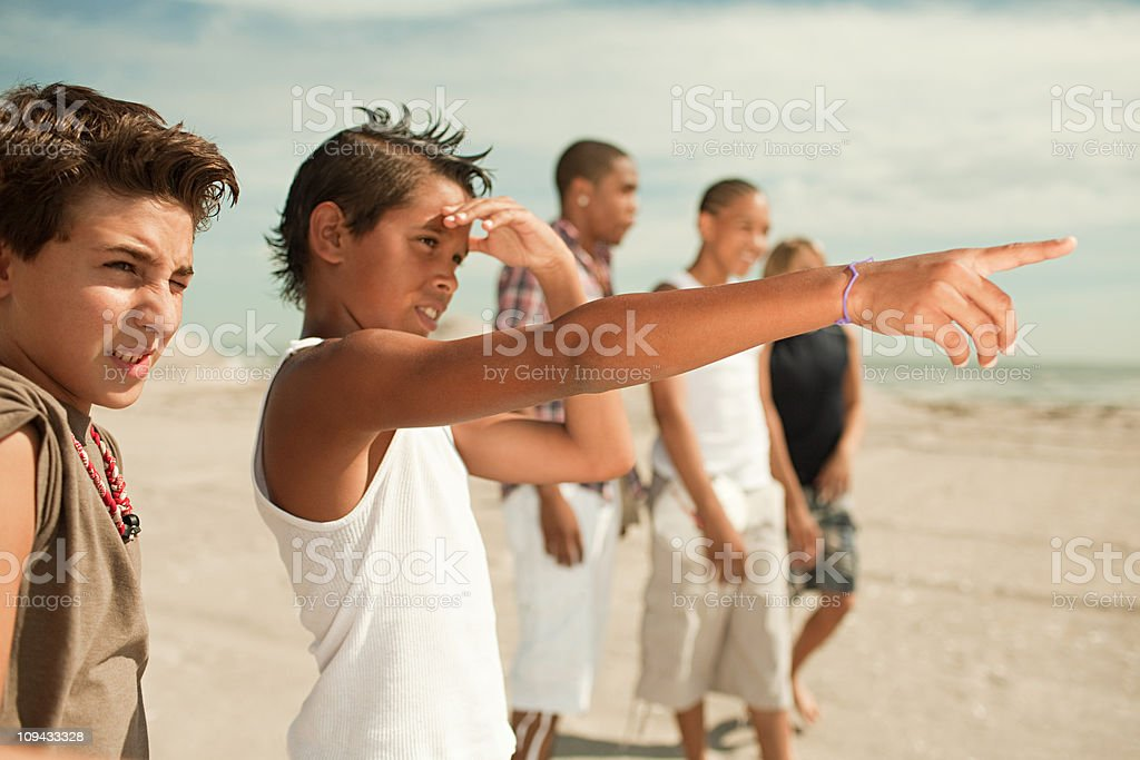 Boys on beach, one boy pointing royalty-free stock photo