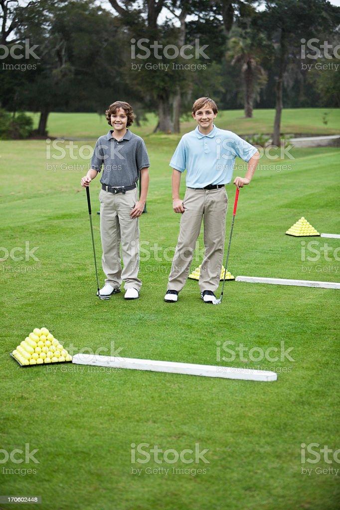 Boys on golf driving range stock photo