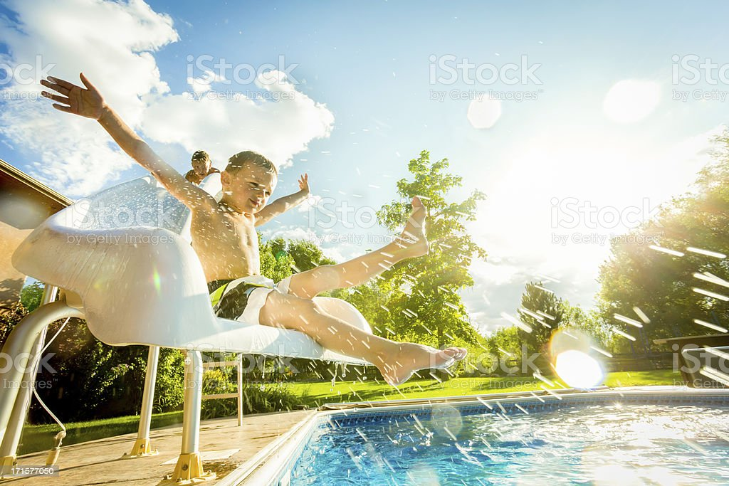 Boys on swimming pool slide stock photo