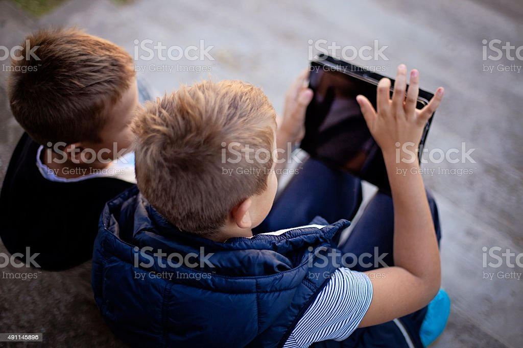 Boys outdoors with a digital tablet digital tablet stock photo