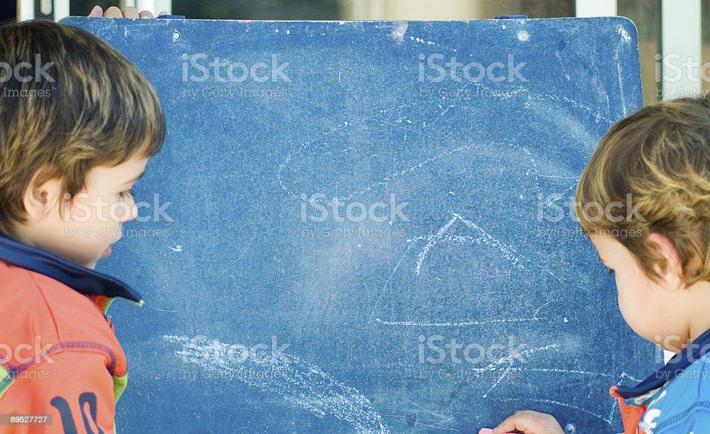 boys painting on a blackboard royalty-free stock photo