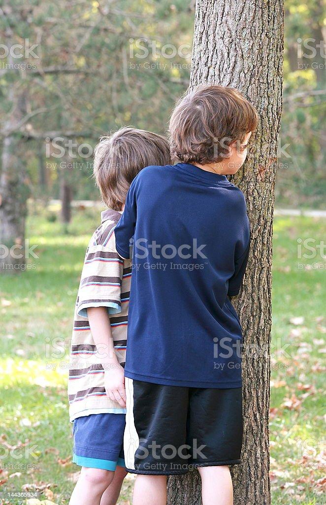 Boys Peeking Around Tree royalty-free stock photo