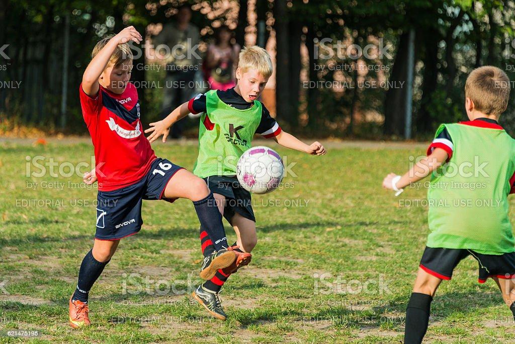 Boys playing football on city football championship among school...