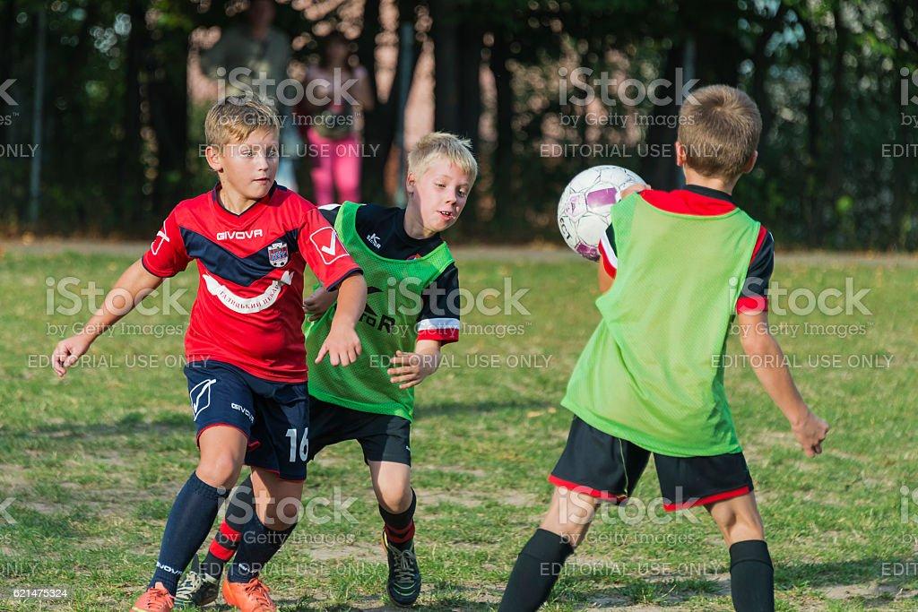 Boys play football on the sports field stock photo