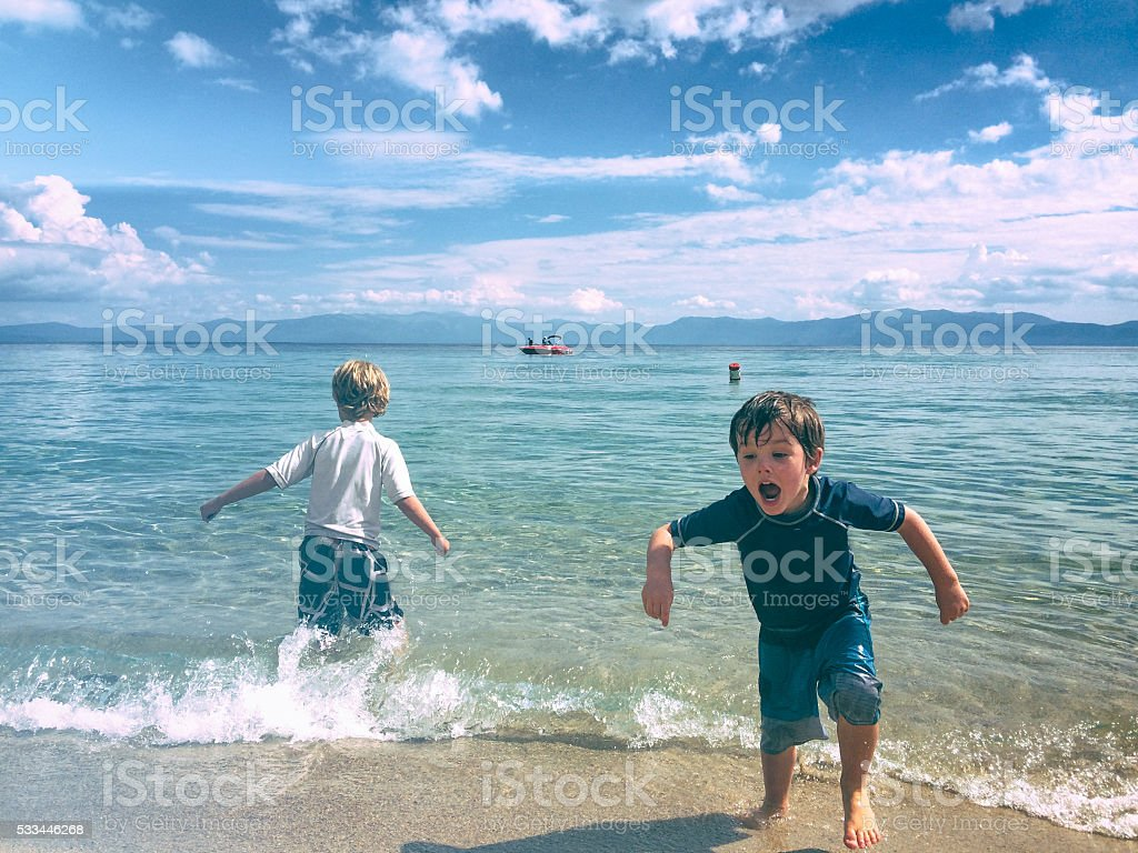 Boys play together in the beautiful waters of Lake Tahoe stock photo