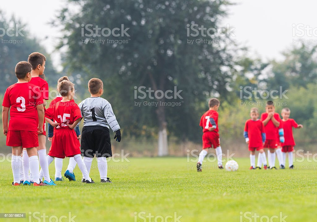 Boys playing football soccer game on sports field stock photo
