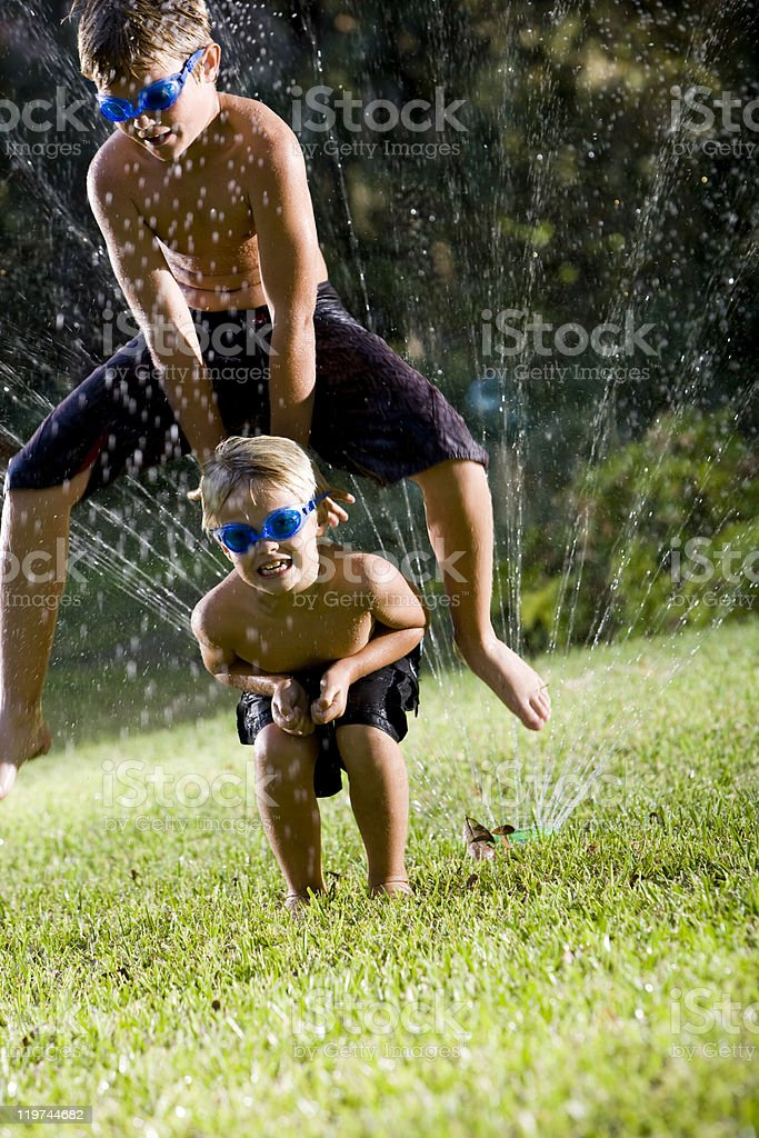 Boys playing leapfrog over lawn sprinkler stock photo