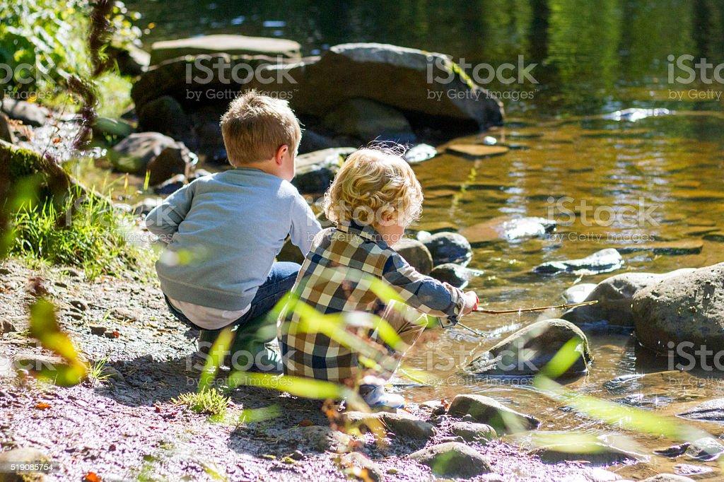 Boys playing next to the lake stock photo