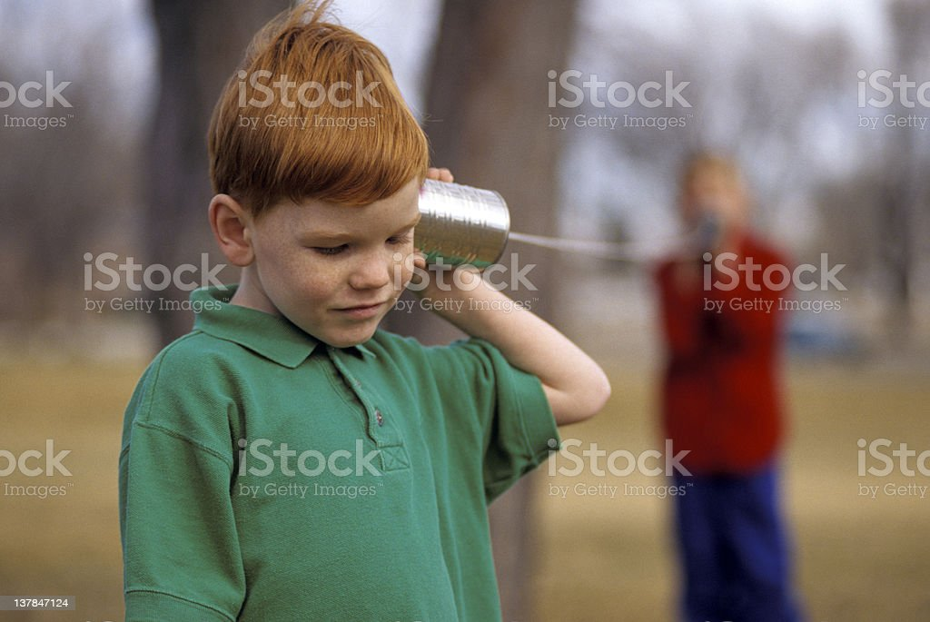 Boys playing on a Can Telephone stock photo