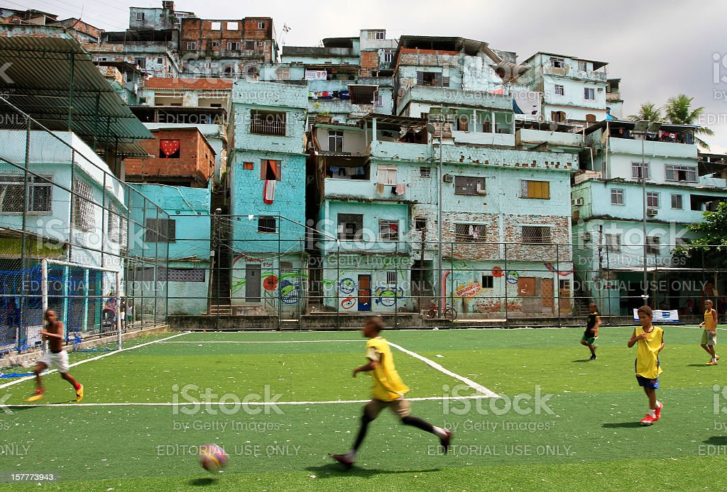 Boys playing soccer in a favela royalty-free stock photo
