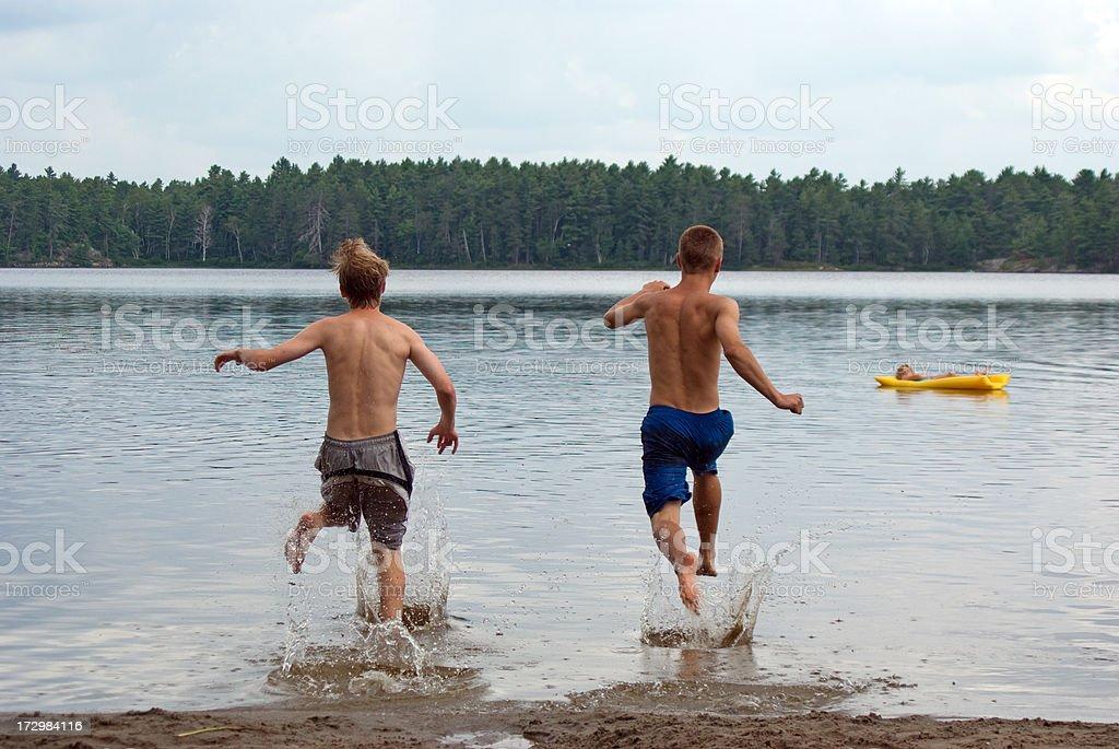 Boys Racing into Lake royalty-free stock photo