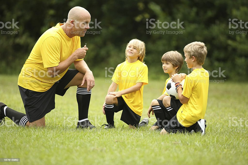Boys Soccer Team Listening To Coach On Field stock photo