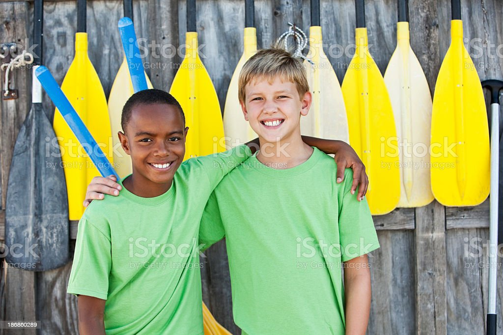 Boys standing in front of paddles royalty-free stock photo