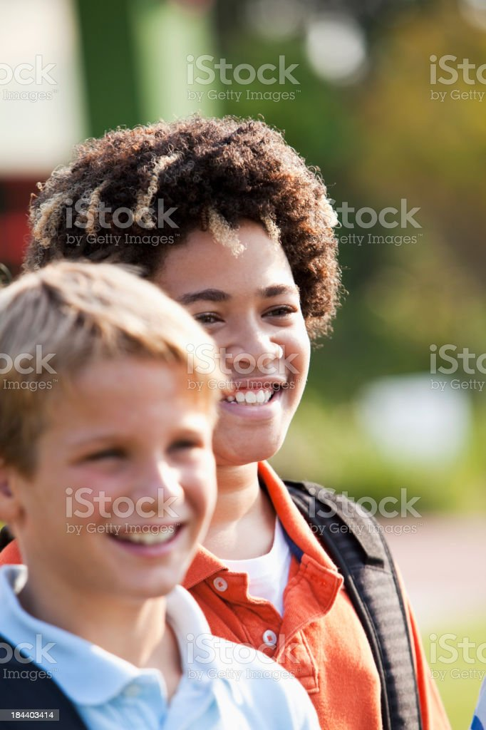 Boys standing outside school with bookbags stock photo