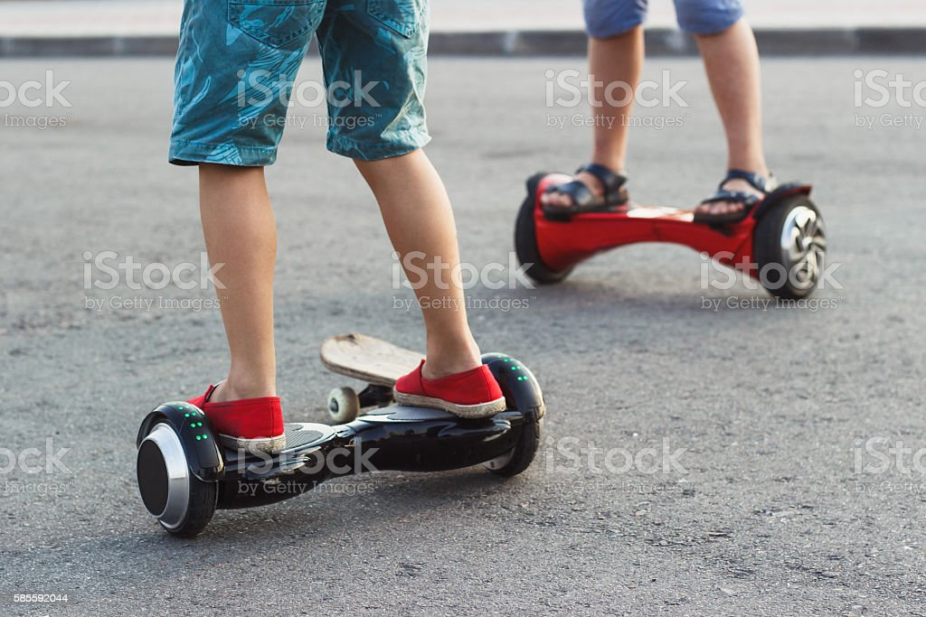 Boys stands on the black gyro scooter outdoors stock photo