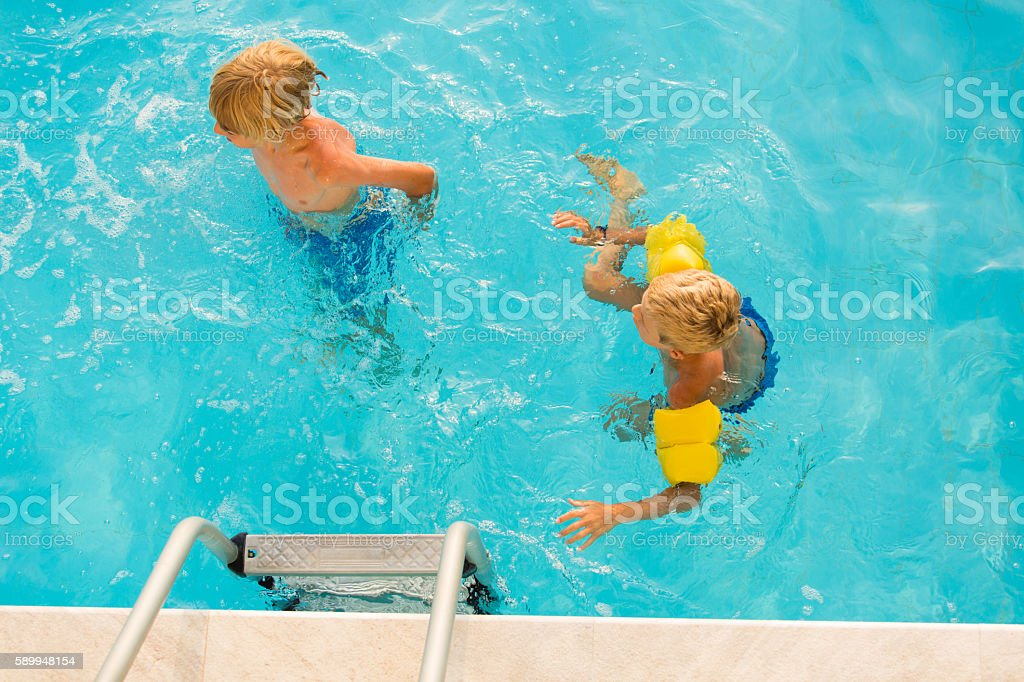 Boys swimming in the pool stock photo