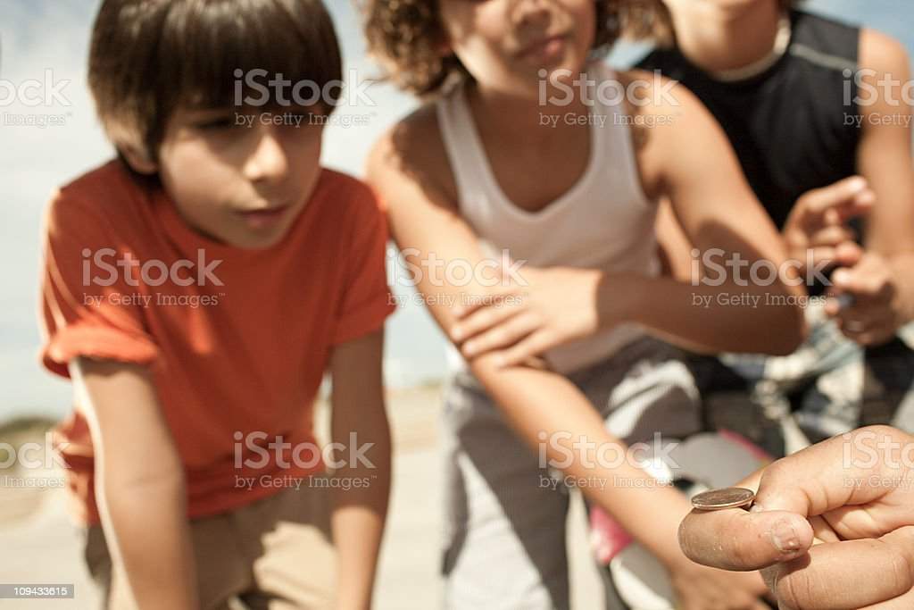 Boys tossing a coin royalty-free stock photo