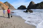 Boys walking along scenic Pfeiffer Beach, California
