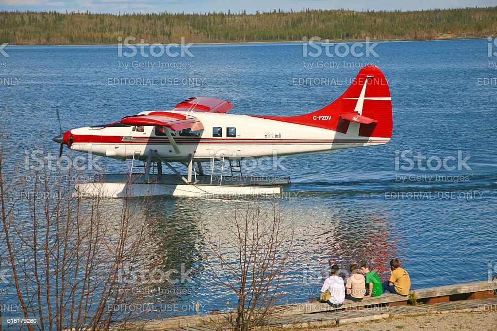Boys Watching a Seaplane Taxying to Landing stock photo