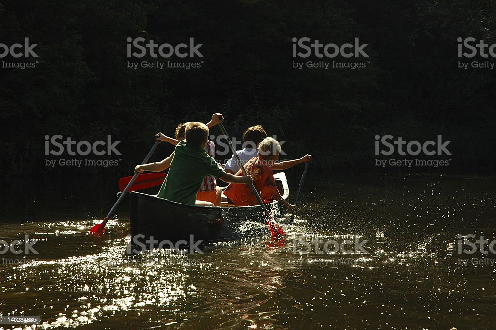 Boys working as a team in canoe royalty-free stock photo