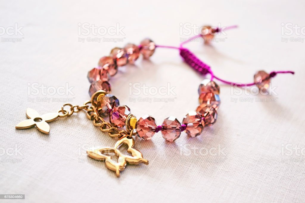 bracelet with purple beads and golden charms stock photo