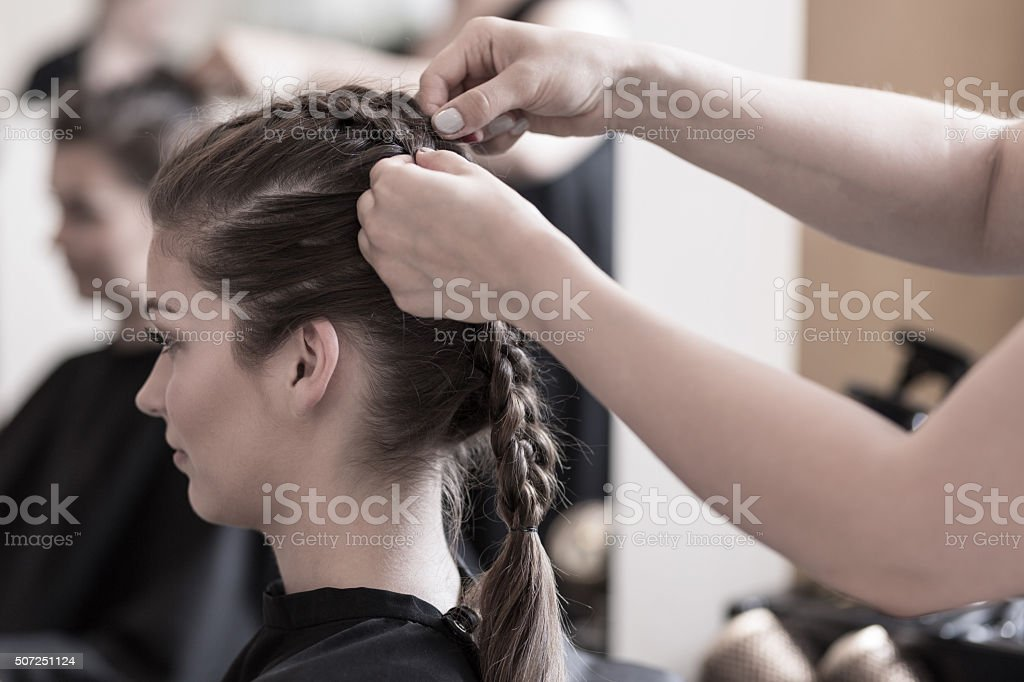 Braiding young woman's hair stock photo