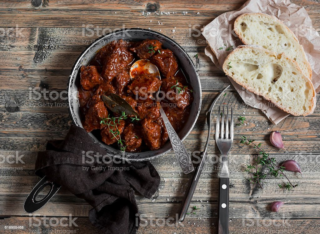 Braised beef in a frying pan on a wooden rustic table. stock photo