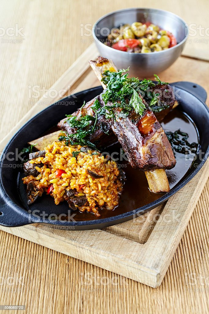 Braised lamb shanks served with bulgur stock photo