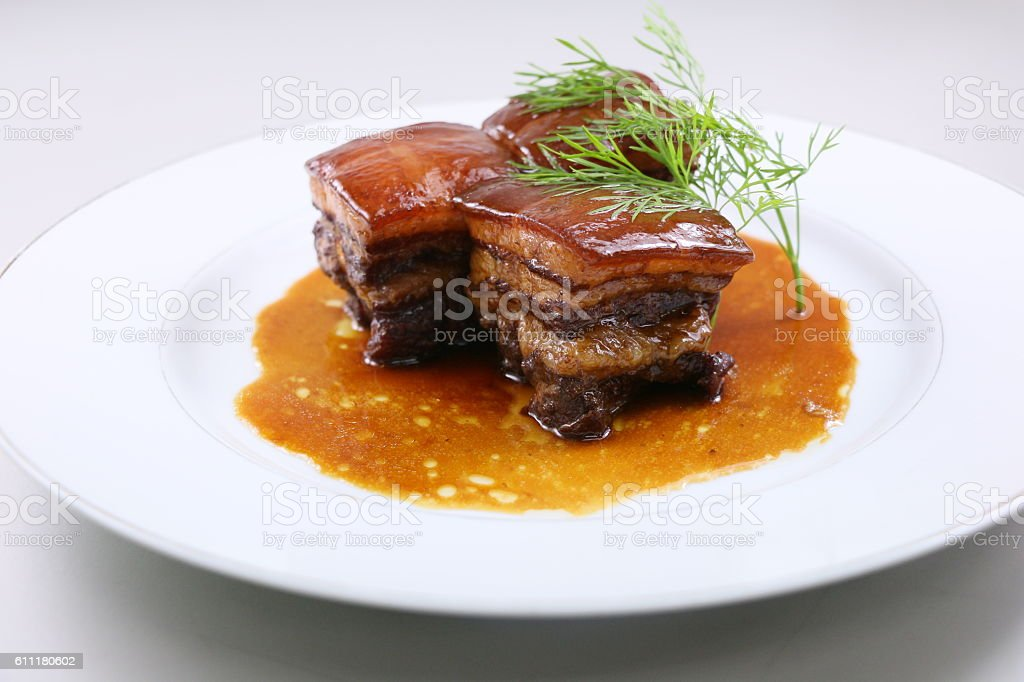 Braised pork meat in Chinese style with herbs on white stock photo