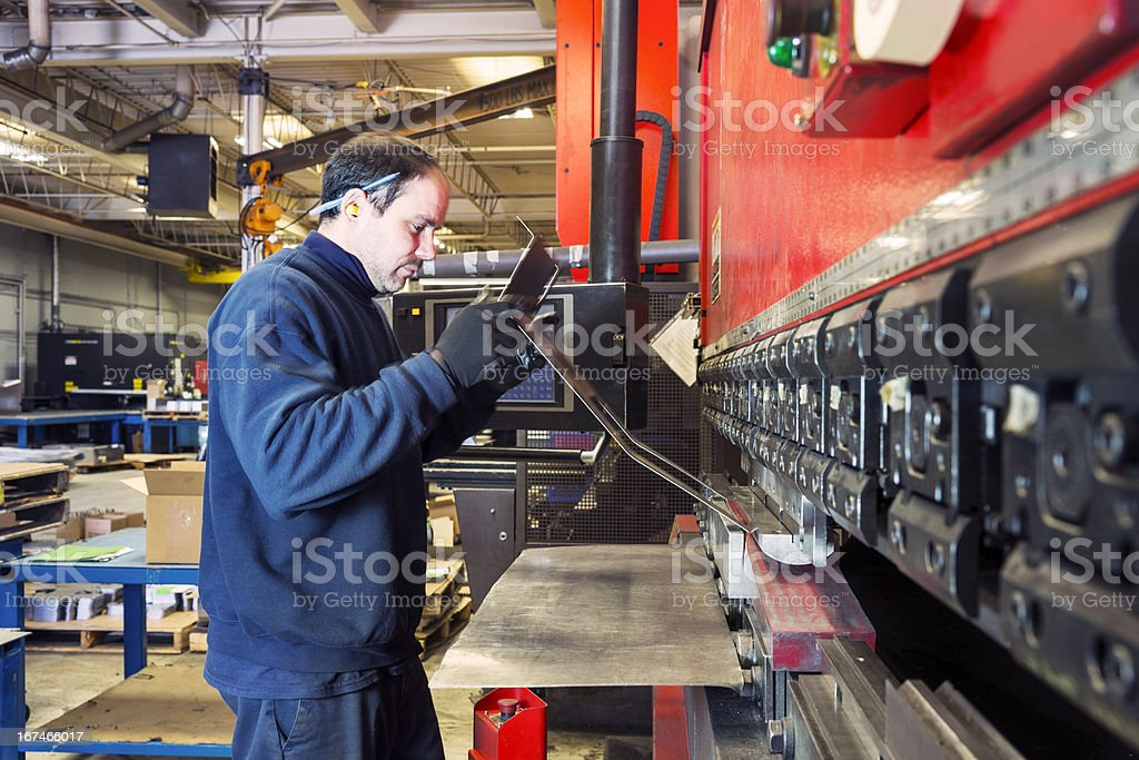 Brake press operator at work in a metalworking factory stock photo