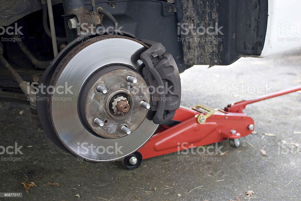 A brake rotor on a car that is jacked up stock photo