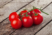 branch of cherry tomatoes on wooden background