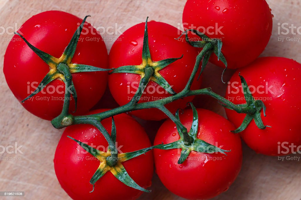 Branch of fleshy tomatoes on a wooden table closeup stock photo
