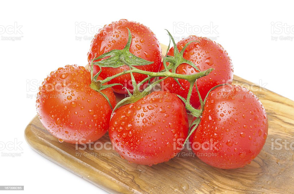 branch of fresh tomatoes on wooden board isolated royalty-free stock photo