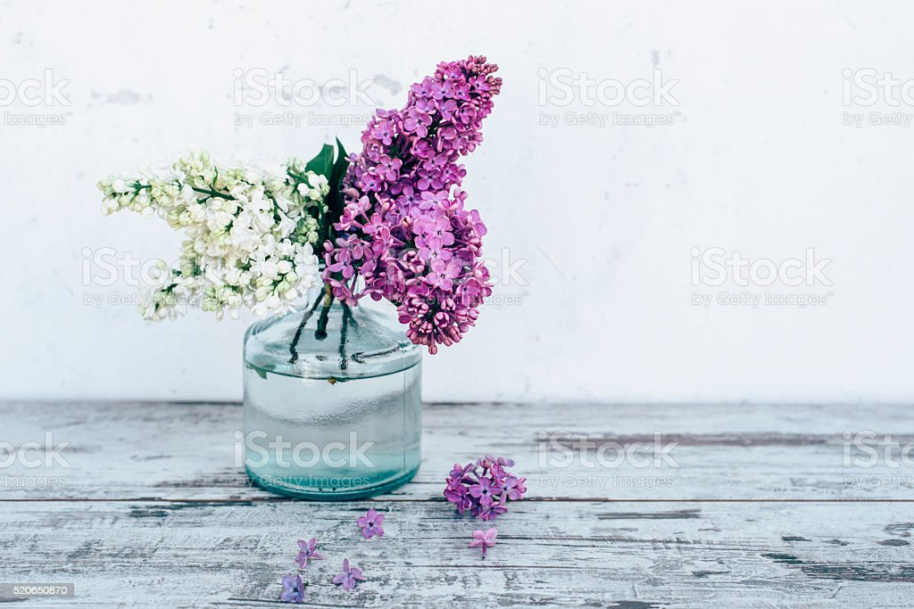 Branches of lilac in glass vase on wooden table stock photo