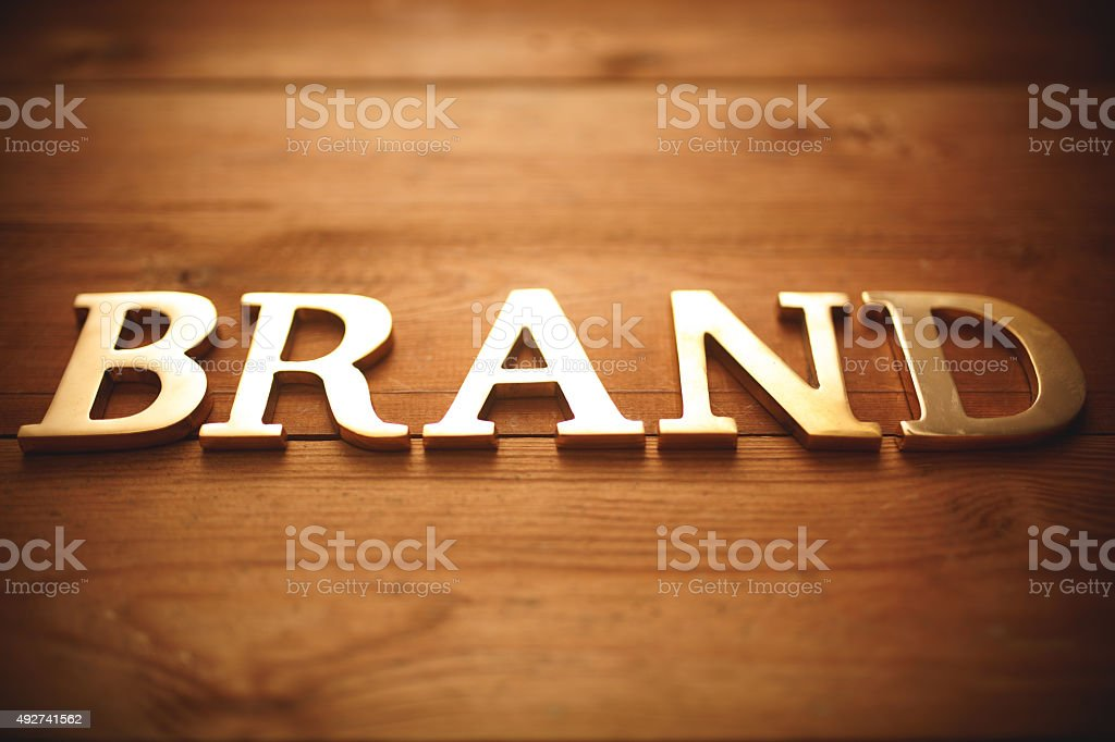 Brand - Golden text on wood stock photo