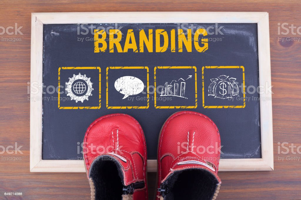 Branding and kid shoes on on chalkboard and wooden background stock photo