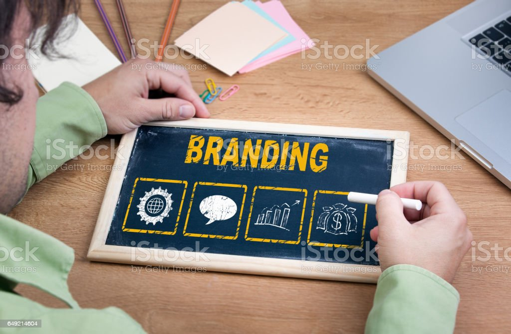 Branding. Chalkboard and a portable computer on wooden office desk stock photo