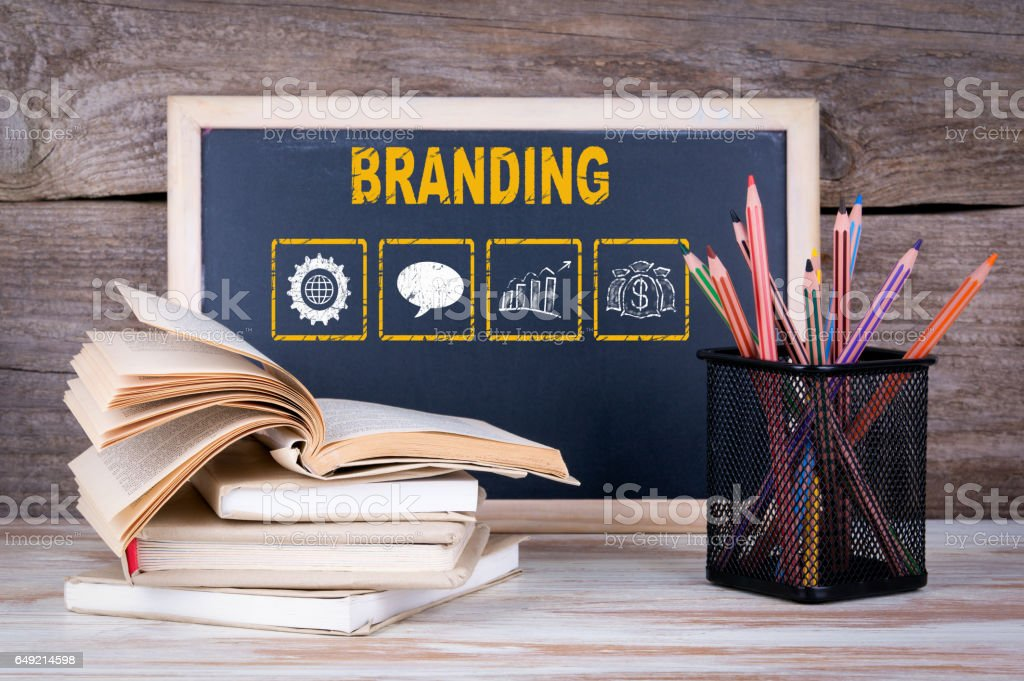 Branding concept. Stack of books, chalk blackboard with pencils on the wooden table. stock photo