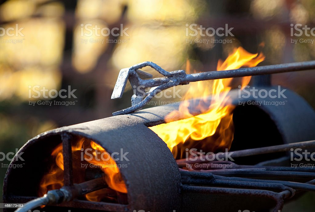 A branding iron and a lit flame stock photo