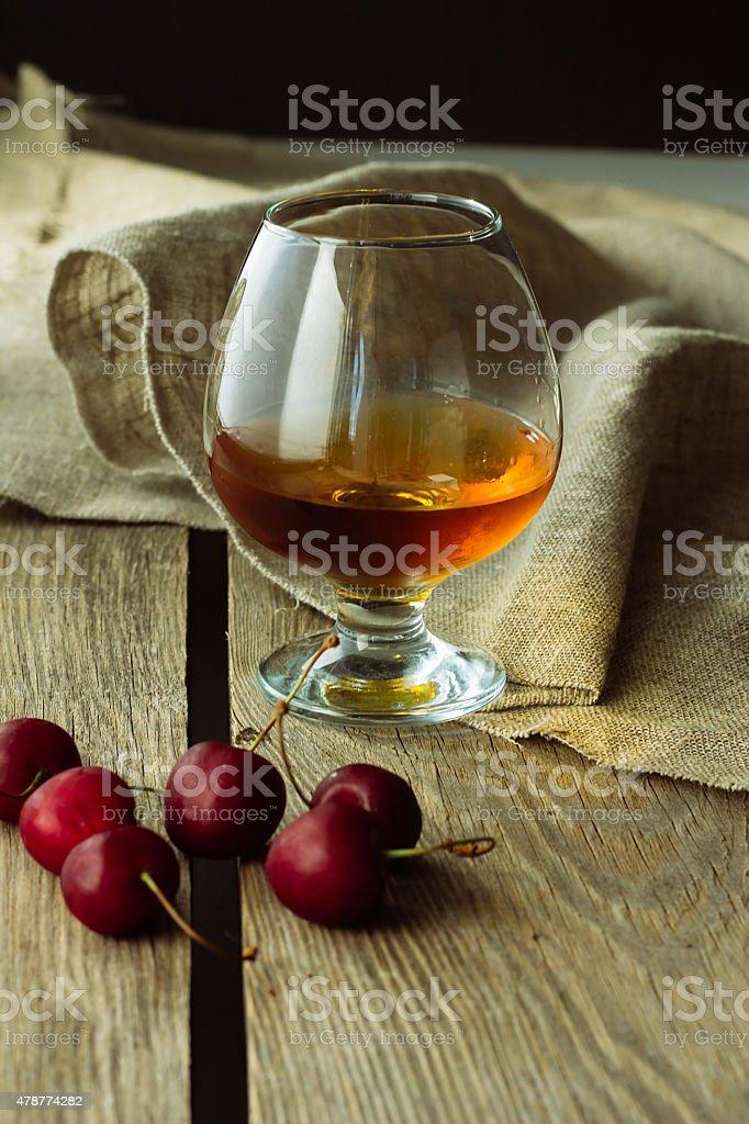 Brandy glass and black cherry stock photo