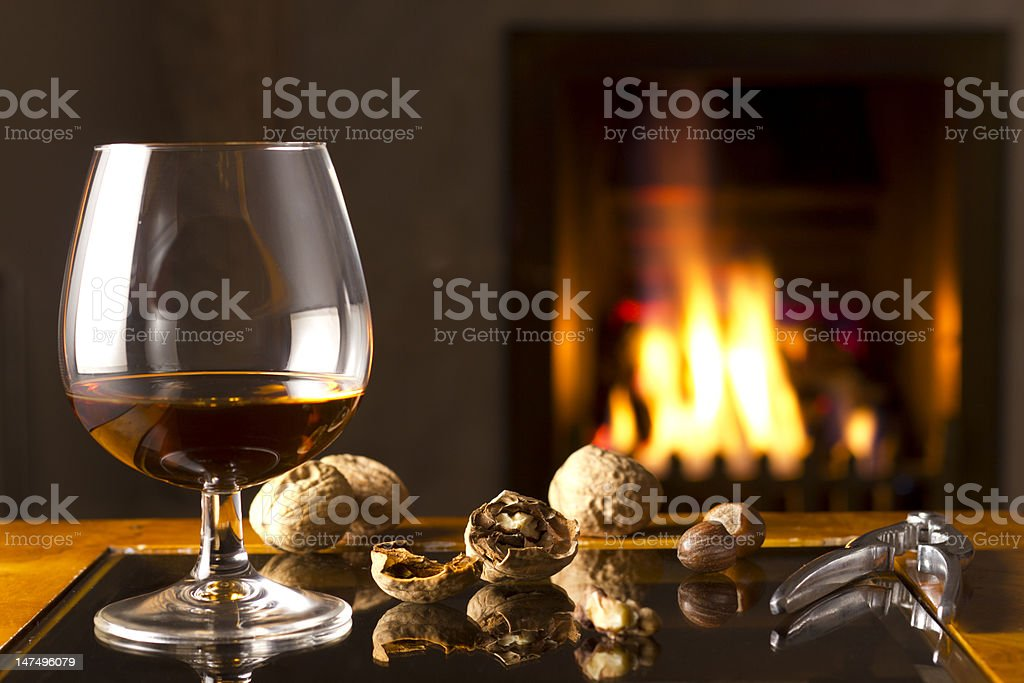 Brandy Snifter and cracked nuts by the fireplace stock photo