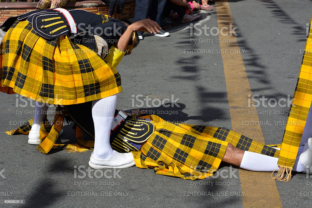 Brass band member fainted on street carried away by colleagues stock photo